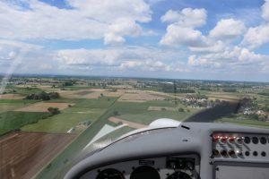 Blick nach vorne aus dem Cockpit des Flugzeugs. Das Flugzeug befindet sich noch einiger Entfernung von dem geplanten Landepunkt.