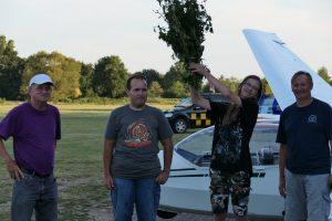 Drei Fluglehrer und ein Flugschüler stehen vor einem Segelflugzeug. Der Flugschüler hat einen Strauß Wildblumen in der Hand.