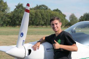 """Eine Person steht vor einem Flugzeug und macht eine """"Daumen hoch""""-Geste."""