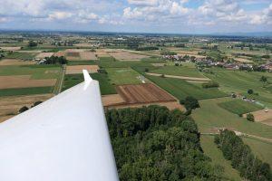 Der linke Flügel eines Motorseglers im Flug über einer Landschaft aus Wiesen und Feldern.
