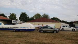 Ein Auto mit Segelfluganhänger steht vor den Hangar am Flugplatz Kehl.