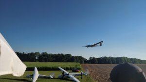 Im oberen Bereich ist ein Segelflugzeug im Landeanflug. Am Boden stehen zwei Segelflugzeuge.