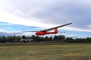 Ein rotes Segelflugzeug in Holzbauweise im Landeanflug