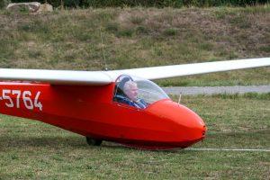 Ein Segelflugzeug (roter Rumpf, weiße Flügel) steht am Start