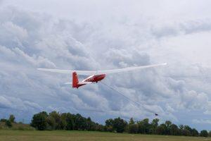 Ein Segelflugzeug (roter Rumpf, weiße Flügel) wird beim Start mit einem Schleppseil gezogen