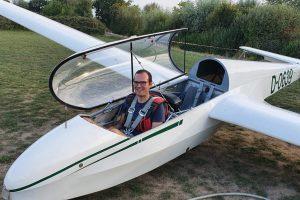 Dominik sitzt im Pilotensitz des am Boden stehenden Segelflugzeugs.
