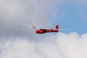 Ein rotes Segelflugzeug vom Typ Ka-8 schwebt mit ausgefahrenen Klappen.