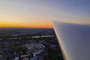 Blick aus dem Flugzeug über den rechten Flügel. Der Himmel ist durch die Dämmerung am Horizont orange gefärbt. Im unteren Teil des Bildes ist Kehl zu sehen.