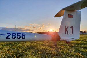 Das Heck eines Segelfligzeugs vom Typ ASK-21. Das Segelflugzeug ist am Boden geparkt und es ist bereits die Heckrolle zum Rangieren angebracht. Im Hintergrund ist die untergehende Sonne zu sehen.