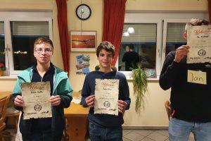 """Drei Personen stehen mit Siegerurkunde in der Hand nebeneinander. Die Person ganz rechts hält die Siegerurkunde vor dem Gesicht und trägt ein Schild mit der Aufschrift """"Jan""""."""