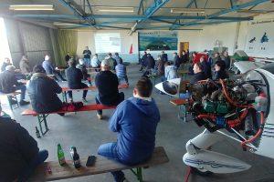 Foto der Versammlung im Hangar. Die Teilnehmer sitzen auf in großen Abständen aufgestellten Bierbänken, wobei immer nur zwei Teilnehmer auf den jeweils entgegengesetzen Enden einer Bank sitzen.