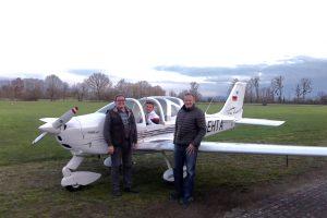 Die Fluglehrer Hubert Heitzmann und Gerd Mätz stehen nach dem Flug vor dem Flugzeug, Maximilian Feißt sitzt im Cockpit.