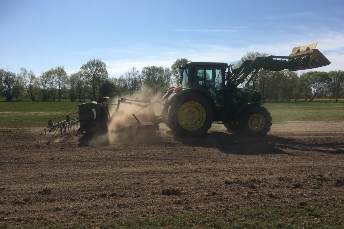 Ein Traktor mit einer Streuvorrichtung fährt über die Piste und sät den Rasen ein.