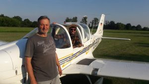 Robin Beyer sitzt im Cockpit und Gerd Mätz steht vor dem Flugzeug.