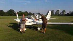 Gerd Mätz und Robin Beyer stehen vor dem Flugzeug und strecken die Händer zueinander zum Handschlag aus ohne sich zu berühren.